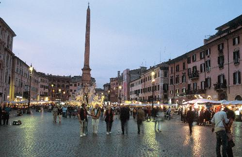 People in the Piazza Navona in Rome at sunset