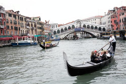 Gondolas along the Grand Canal and Rialto Bridge in background, Venice.