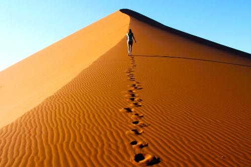 Climbing one of the tallest dunes at sunrise in the Namib-Naukluft National Park in Namibia.
