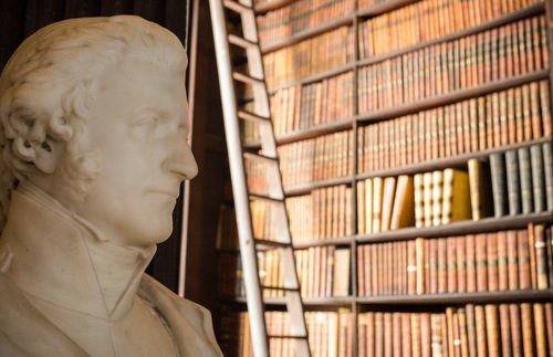 A marble bust and shelves of books inside the Long Room at Trinity College in Dublin