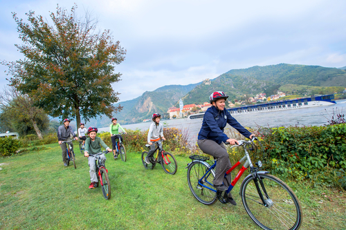 Family biking in Europe with river cruise boat in background