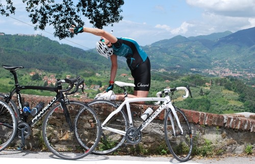 Woman in yoga pose by bike on moutain road in Italy