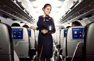 JetBlue flight attendant smiling in aisle