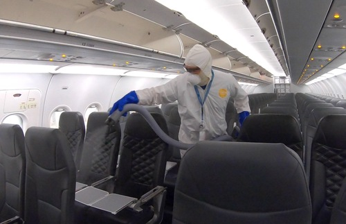 worker fumigates sanitizes Frontier Airlines cabin
