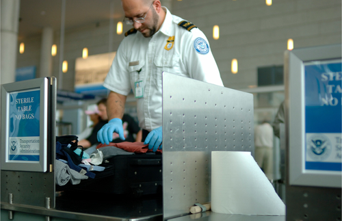 TSA agent searching open luggage at airport