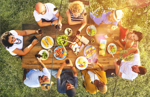 friends dining at outdoor table together, overhead shot
