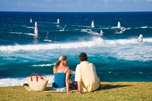 A couple enjoys a picnic overlooking windsurfers, Lower Paia.