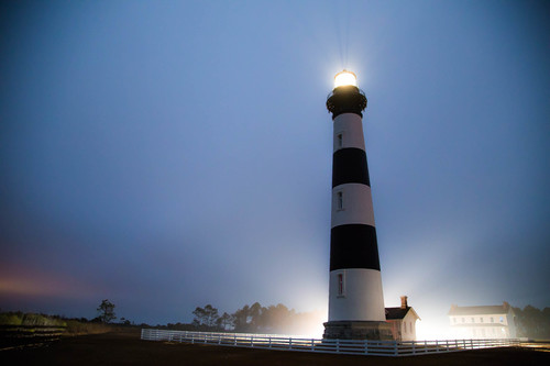Black and white striped lighthouse lit up at night with light shining from behind