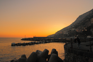 A silhouette of the Amalfi Coastline and an orange sunset.