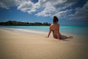 A woman lounges on a beach in Antigua.