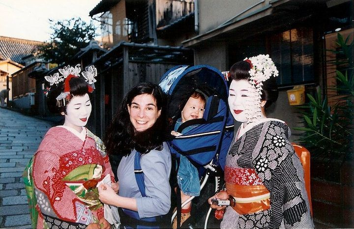 The author and her infant daughter pose with apprentice geishas, in full costume, on the streets of Kyoto