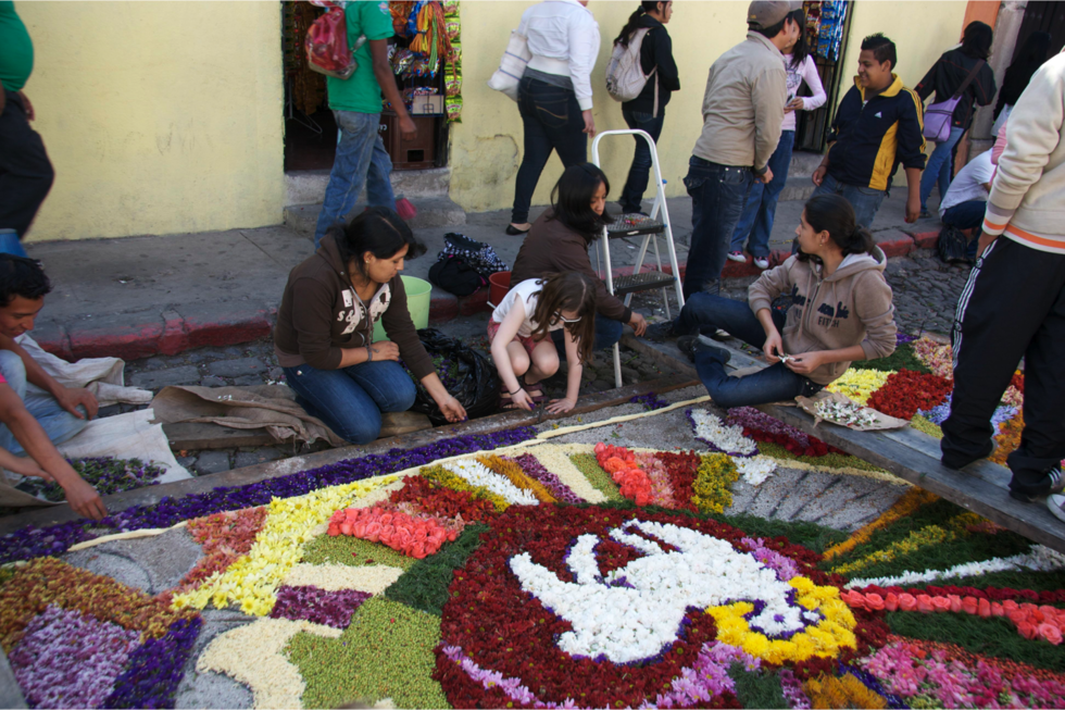The author's daughter helps make an alfombra, or rug of flowers, in honor of Easter celebrations in Antigua, Guatemala