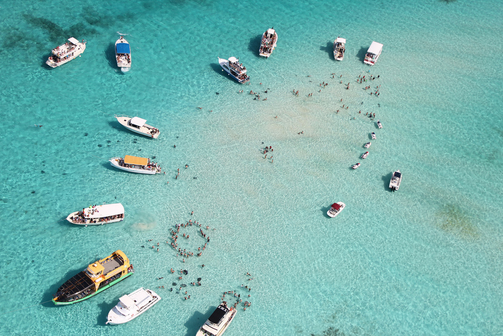 A view from above of boats and divers surrounding them in crystal clear Caribbean water.