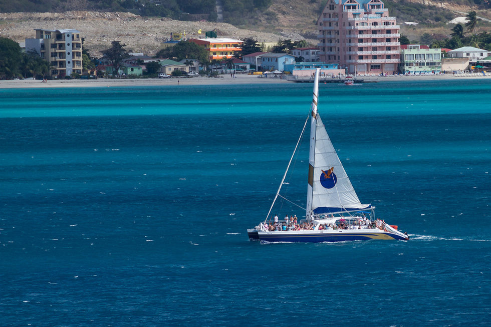 A catamaran on the bright blue Caribbean water of the ocean.