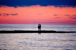 A couple walking down the beach with a pink sunset behind them.