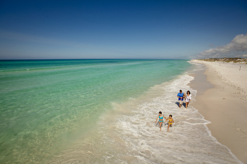 Crystal clear green and blue waters of the Florida ocean washing up onto white sand.