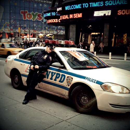 A NYPD officer rests against his car in Times Square