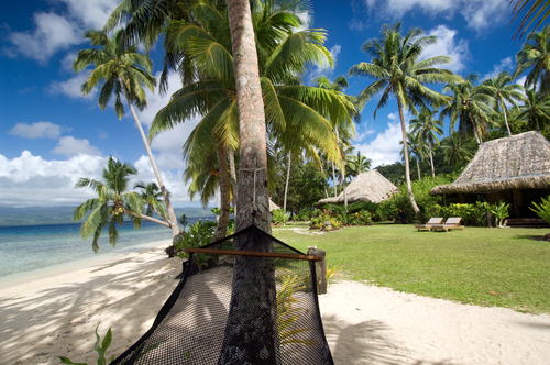 A hammock resting between trees on a white sand beach