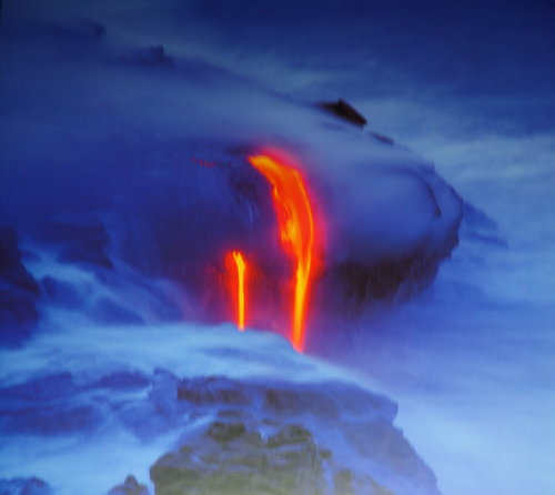 Lava melting down the side of a smoking volcano.