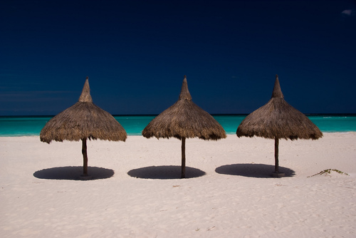 Three tiki huts on a white sandy beach in Riviera Nayarit, Mexico.