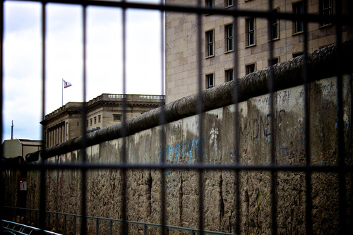 A view of the Berlin wall through a fence.