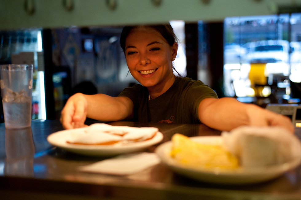 A server dishes up breakfast at T-Coons with a smile