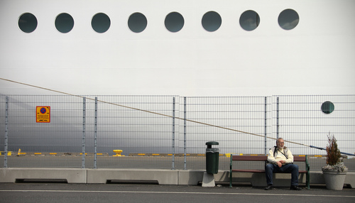 man sitting outside a cruise ship