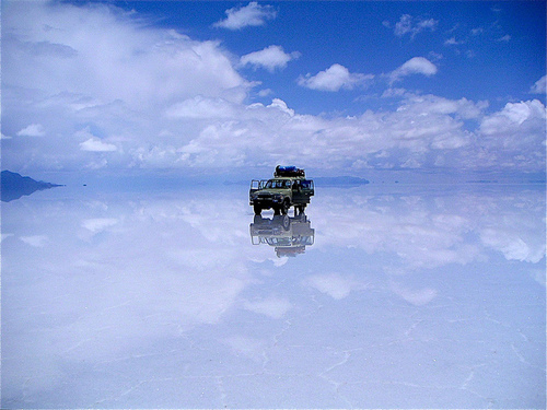A tourist jeep stopped in the middle of Salar de Uyuni, which is covered in a layer of water and reflecting the skies above