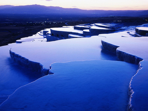 Blue and purple terraced hot springs of Pamukkale seen at dusk