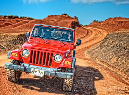 Red Jeep Wrangler off roading on the dirt trails of Lanai.