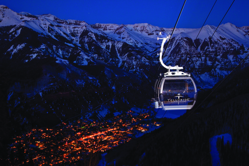 A gondola slides down to a night-lit town of Telluride