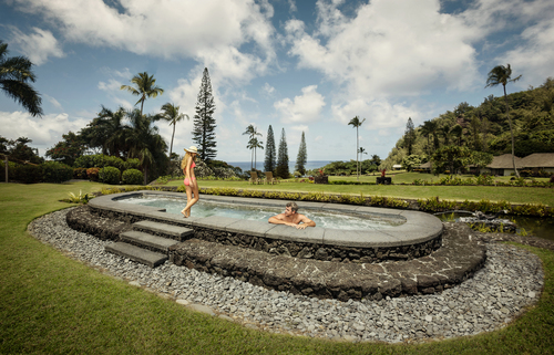 A couple bathes in the lava rock Jacuzzi at the Travaasa Hana resort