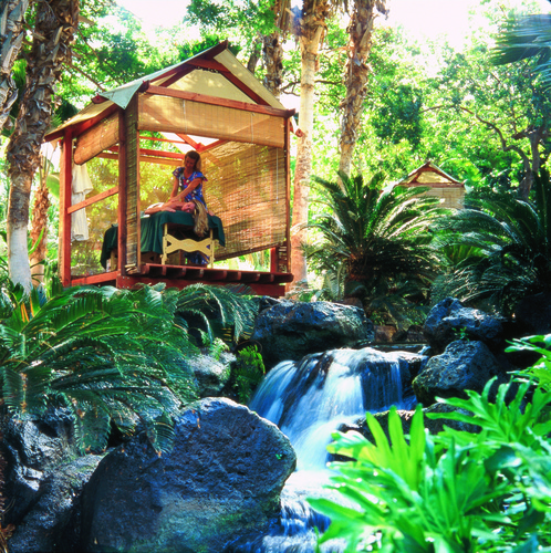 A woman gets a massage in a hut over a waterfall at the Fairmont Orchid Resort.