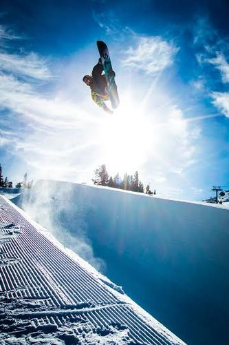 "A snowboarder ""flying"" through striking blue sky at Mammoth resort, California."