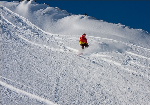 Snowboarding down a powdery slope at Livigno Resort, Italy.