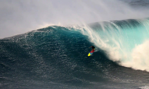 A surfer is challenged by a massive wave