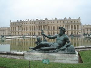 A closeup of the four bronze statues with the Palace of Versaille in the background.