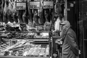 A man standing outside a jamon shop in Spain