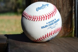 A closeup of a baseball with the Major League Baseball emblem.