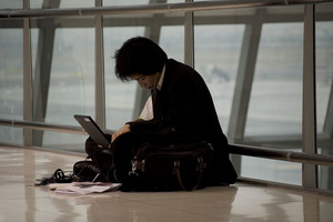 A man sits on the floor of an airport, using his laptop.