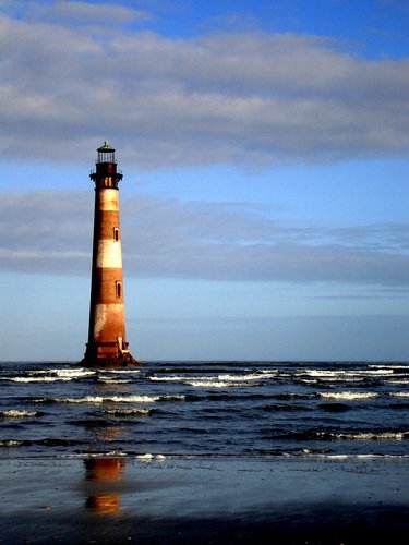 Photo taken from beach of faded brown and white faded lighthouse cast with hues of afternoon light sitting out at sea