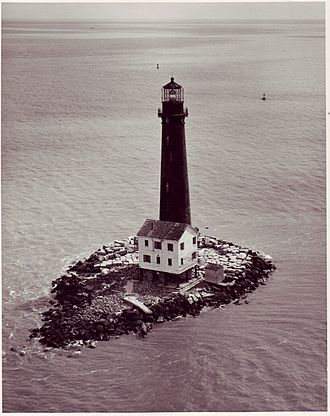 Pictured is a tall, slim black lighthouse with a granite base in the middle of the Gulf Coast on a small rocky island.