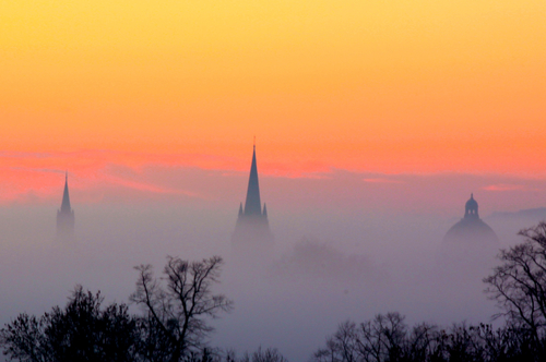 Oxford dreaming spires against orange cloudy sky with tree silhouettes