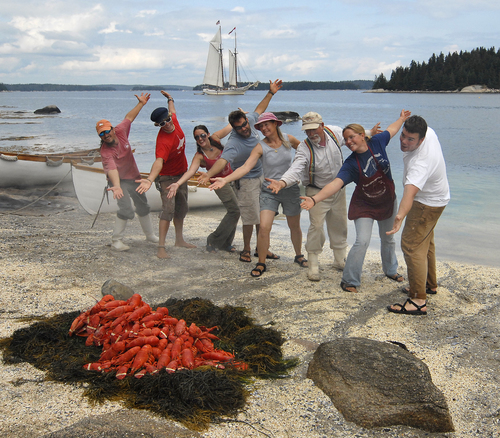 A crew prepares a lobster bake on a beach in Maine.