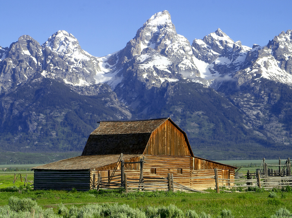 The Grand Tetons loom over an old barn