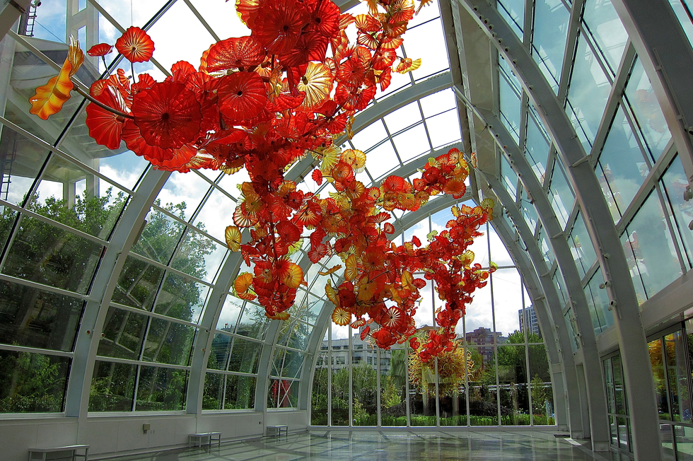 Glasshouse with orange spiral sculpture suspended from ceiling