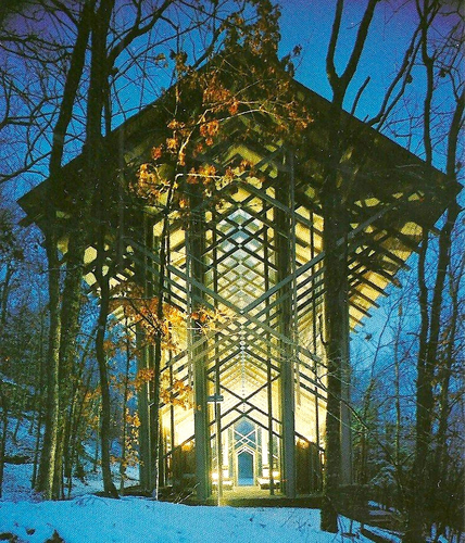 Classic steel and glass chapel lit up at night in a forest