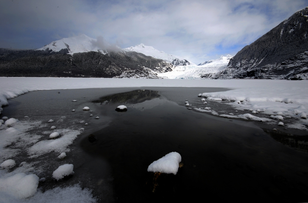 icy lake with glacier and snowy mountains in background