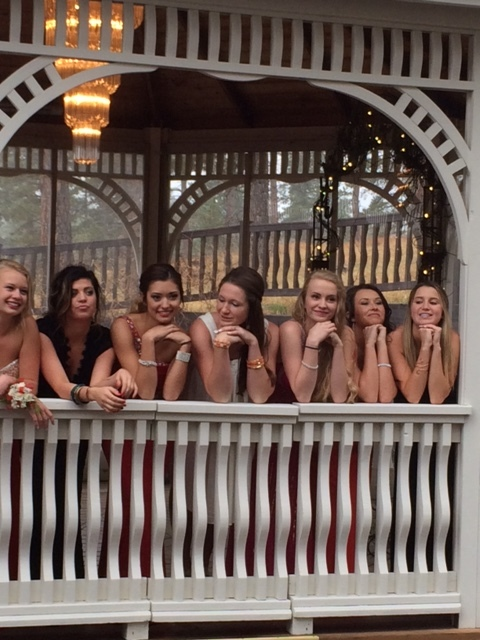 A bride and her bridesmaids hang out on the gazebo