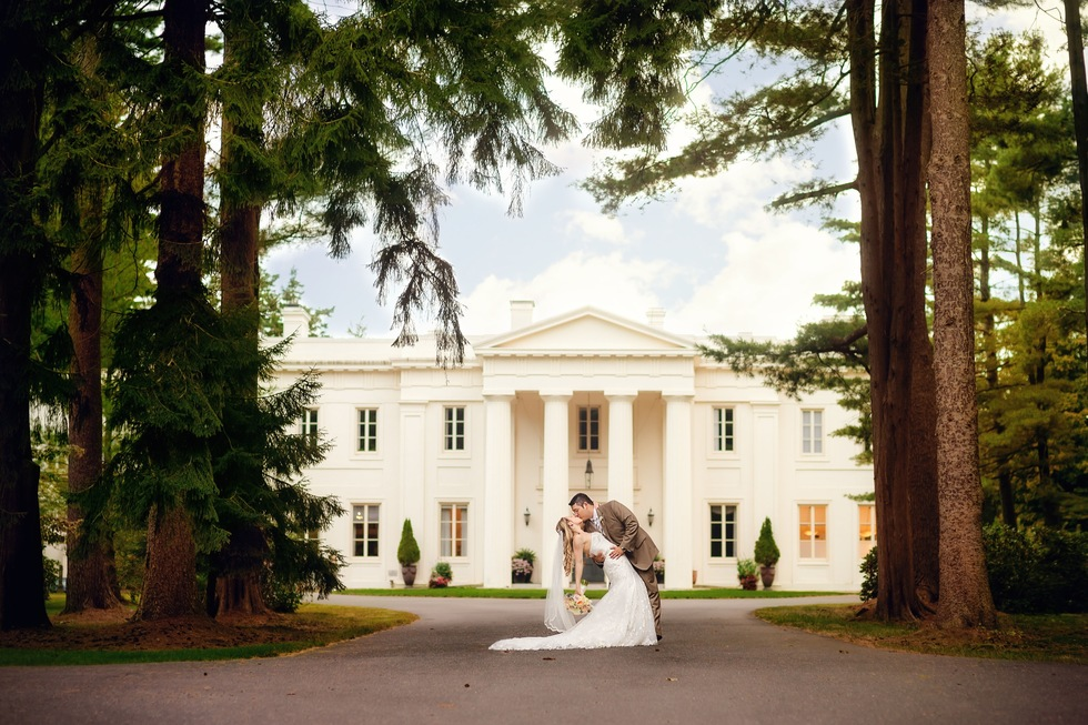 Bride and groom kissing in front pathway of Wadsworth Mansion